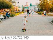 Little girl using a scooter on the city street. Стоковое фото, фотограф Zoonar.com/Max / easy Fotostock / Фотобанк Лори