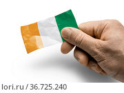 Hand holding a card with a national flag the Cote dIvoire. Стоковое фото, фотограф Zoonar.com/BUTENKOV ALEKSEY / easy Fotostock / Фотобанк Лори