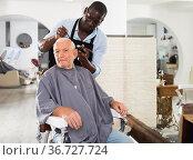 Elderly man getting haircutting from African barber. Стоковое фото, фотограф Яков Филимонов / Фотобанк Лори
