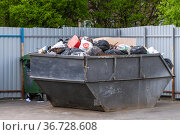 Moscow, Russia - May 16. 2021. Overflowing trash can with plastic bags filled with household rubbish. Редакционное фото, фотограф Володина Ольга / Фотобанк Лори