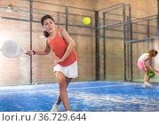 Young asian woman playing padel on a hard court. Стоковое фото, фотограф Яков Филимонов / Фотобанк Лори