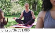 Caucasian man meditating and practicing yoga at the park. Стоковое видео, агентство Wavebreak Media / Фотобанк Лори
