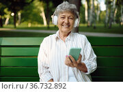 Old woman in headphones listens to music on bench. Стоковое фото, фотограф Tryapitsyn Sergiy / Фотобанк Лори