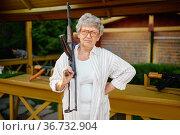 Pretty granny with gun poses in shooting gallery. Стоковое фото, фотограф Tryapitsyn Sergiy / Фотобанк Лори