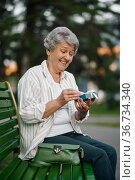 Cheerful granny opens a gift box on the bench. Стоковое фото, фотограф Tryapitsyn Sergiy / Фотобанк Лори