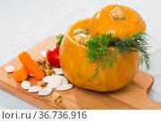 Tasty homemade pumpkin soup puree served in pumpkin at wooden desk. Стоковое фото, фотограф Яков Филимонов / Фотобанк Лори