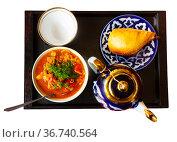 Uzbek laghman, samsa, teapot and cup on tray. Стоковое фото, фотограф Яков Филимонов / Фотобанк Лори