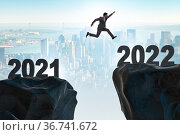 Man jumping from year 2021 to 2022. Стоковое фото, фотограф Elnur / Фотобанк Лори