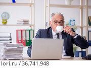 Old male employee feeling bad at workplace. Стоковое фото, фотограф Elnur / Фотобанк Лори