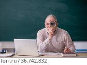 Old male teacher in front of blackboard. Стоковое фото, фотограф Elnur / Фотобанк Лори