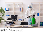 Old male contractor in office disinfection concept. Стоковое фото, фотограф Elnur / Фотобанк Лори