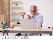 Old male dentist in telemedicine concept. Стоковое фото, фотограф Elnur / Фотобанк Лори