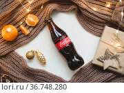 Christmas mood concept. Cozy composition with plaid, coca cola, tangerines and traditional festive decorations. Belarus, Minsk, 15.10.21. Редакционное фото, фотограф Galina kondratenko / Фотобанк Лори