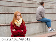 Young couple in a quarrel, a guy and a girl are sitting far from each other in the empty stands. Стоковое фото, фотограф Евгений Харитонов / Фотобанк Лори
