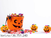 Composition of halloween bucket with trick or treat sweets, spider and pumpkins on white background. Стоковое фото, агентство Wavebreak Media / Фотобанк Лори