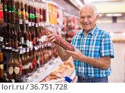 old age man examines salami in sausage department of supermarket. Стоковое фото, фотограф Татьяна Яцевич / Фотобанк Лори