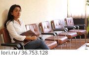 Smiling confident Hispanic woman waiting for job interview, sitting on chair in office corridor, looking at camera. Стоковое видео, видеограф Яков Филимонов / Фотобанк Лори