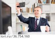 Male business consultant working in an office takes a selfie. Стоковое фото, фотограф Яков Филимонов / Фотобанк Лори