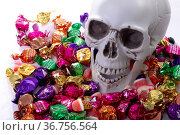 Composition of halloween laughing skull with trick or treat sweets on white background. Стоковое фото, агентство Wavebreak Media / Фотобанк Лори