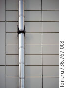 Ein montiertes Edelstahlrohr an einer symmetrisch angeordneten Blechfassade... Стоковое фото, фотограф Zoonar.com/Bastian Kienitz / easy Fotostock / Фотобанк Лори