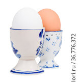 Side view of pair of boiled eggs in ceramic egg cups isolated on white... Стоковое фото, фотограф Zoonar.com/Valery Voennyy / easy Fotostock / Фотобанк Лори