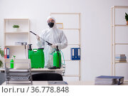 Young male contractor disinfecting office during pandemic. Стоковое фото, фотограф Elnur / Фотобанк Лори