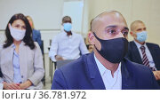 Side view of managers group in protective masks working at laptops in company office. Стоковое видео, видеограф Яков Филимонов / Фотобанк Лори