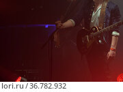 Guitarist with an electric guitar stands on a stage. Стоковое фото, фотограф EugeneSergeev / Фотобанк Лори