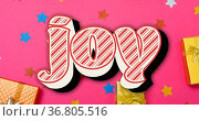 Composition of joy text over christmas presents and decorations on pink background. Стоковое фото, агентство Wavebreak Media / Фотобанк Лори