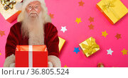 Composition of smiling santa claus holding present over presents on pink background at christmas. Стоковое фото, агентство Wavebreak Media / Фотобанк Лори