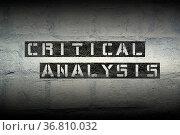 Critical analysis stencil print on the grunge white brick wall. Стоковое фото, фотограф Zoonar.com/Yury Zap / easy Fotostock / Фотобанк Лори