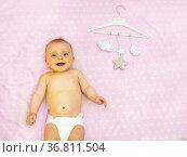 Little laughing baby girl, mobile toys on hanger. Стоковое фото, фотограф Сергей Новиков / Фотобанк Лори
