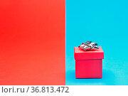 Ein rotes Geschenk vor einem blau-rotem Hintergrund. Стоковое фото, фотограф Zoonar.com/Ulrich Schade / easy Fotostock / Фотобанк Лори
