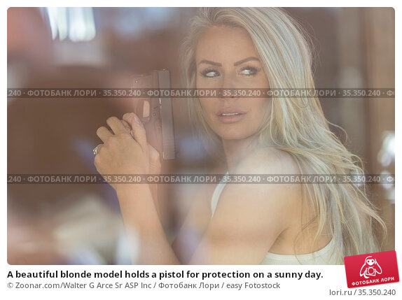 A beautiful blonde model holds a pistol for protection on a sunny day. Стоковое фото, фотограф Zoonar.com/Walter G Arce Sr ASP Inc / easy Fotostock / Фотобанк Лори