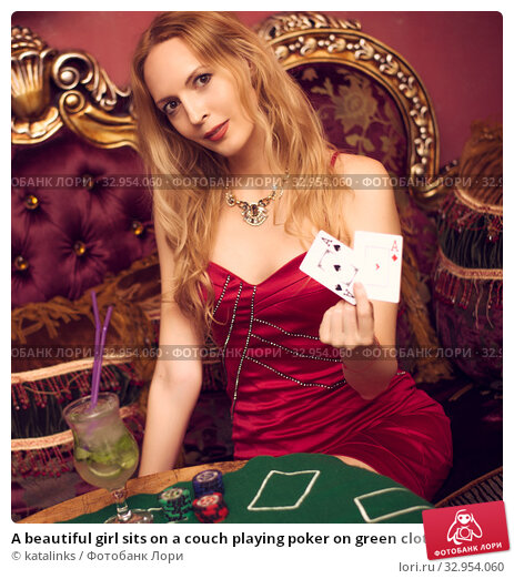 A beautiful girl sits on a couch playing poker on green cloth and holds playing cards in her hands. Стоковое фото, фотограф katalinks / Фотобанк Лори