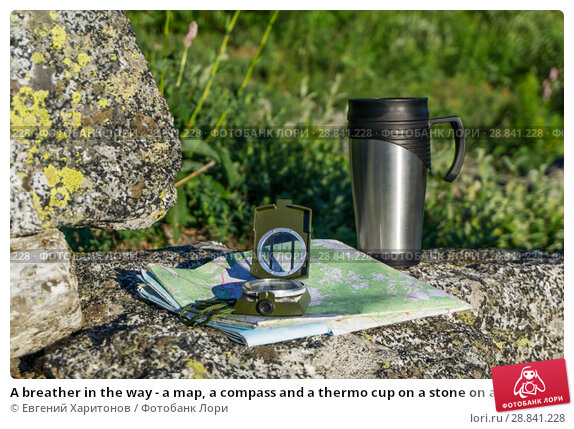 Купить «A breather in the way - a map, a compass and a thermo cup on a stone on a natural background», фото № 28841228, снято 21 июля 2018 г. (c) Евгений Харитонов / Фотобанк Лори