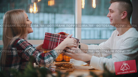 A couple in cafe eating waffles - a man gives his girlfriend a christmas gift. Стоковое видео, видеограф Константин Шишкин / Фотобанк Лори