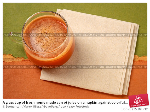 A glass cup of fresh home made carrot juice on a napkin against colorful... Стоковое фото, фотограф Zoonar.com/Marek Uliasz / easy Fotostock / Фотобанк Лори