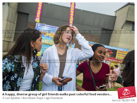 A happy, diverse group of girl friends walks past colorful food vendors... Стоковое фото, фотограф Lori Epstein / age Fotostock / Фотобанк Лори