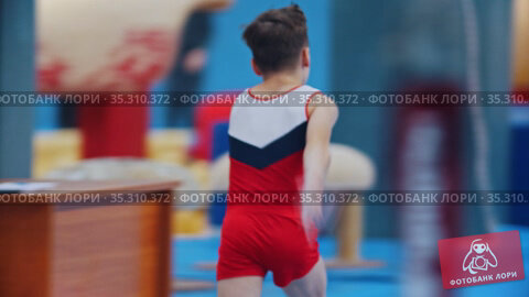 A little gymnastics boy jumping over the barrier on the tournament. Стоковое видео, видеограф Константин Шишкин / Фотобанк Лори