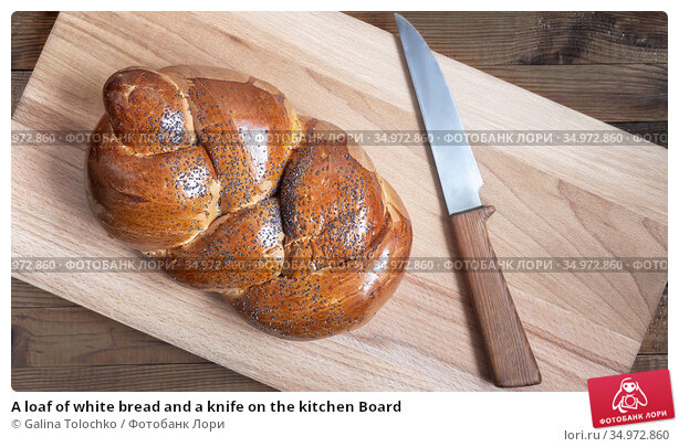 A loaf of white bread and a knife on the kitchen Board. Стоковое фото, фотограф Galina Tolochko / Фотобанк Лори