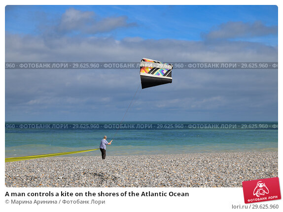 Купить «A man controls a kite on the shores of the Atlantic Ocean», фото № 29625960, снято 11 сентября 2018 г. (c) Ирина Аринина / Фотобанк Лори