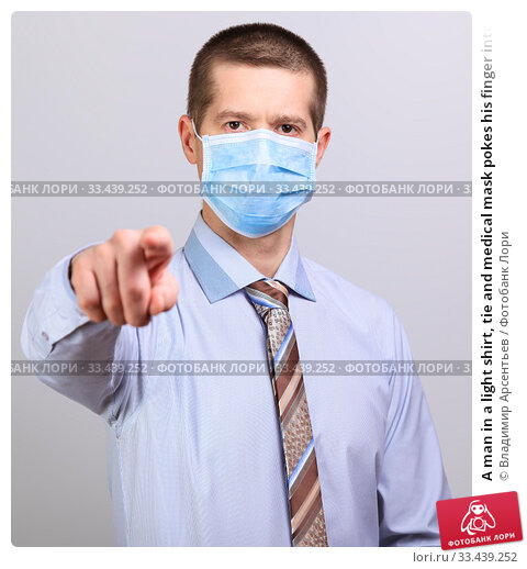 Купить «A man in a light shirt, tie and medical mask pokes his finger into a cell isolated», фото № 33439252, снято 26 марта 2020 г. (c) Владимир Арсентьев / Фотобанк Лори