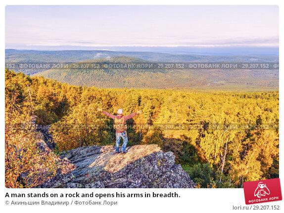 Купить «A man stands on a rock and opens his arms in breadth.», фото № 29207152, снято 6 сентября 2017 г. (c) Акиньшин Владимир / Фотобанк Лори