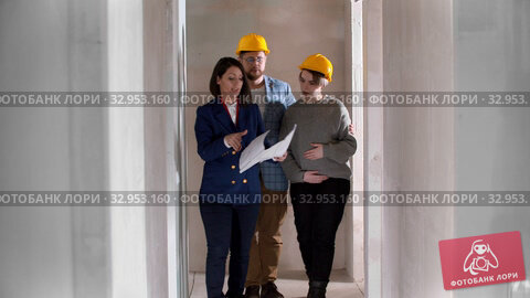 A real estate agent showing a new draft apartment to a young married couple in yellow helmets holding a layout on the paper. Стоковое видео, видеограф Константин Шишкин / Фотобанк Лори