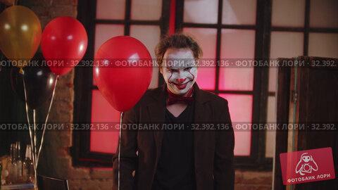 Купить «A smiling scary clown in the brown jacket holding a red balloon», видеоролик № 32392136, снято 14 ноября 2019 г. (c) Константин Шишкин / Фотобанк Лори