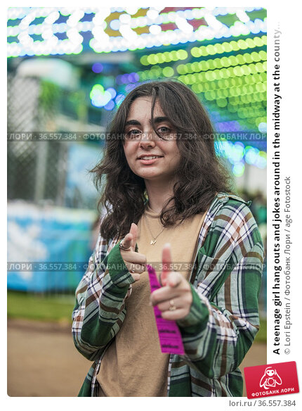 A teenage girl hang outs and jokes around in the midway at the county... Стоковое фото, фотограф Lori Epstein / age Fotostock / Фотобанк Лори