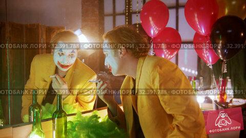Купить «A tired man clown smoking in the dressing room and looking in the mirror», видеоролик № 32391788, снято 14 ноября 2019 г. (c) Константин Шишкин / Фотобанк Лори