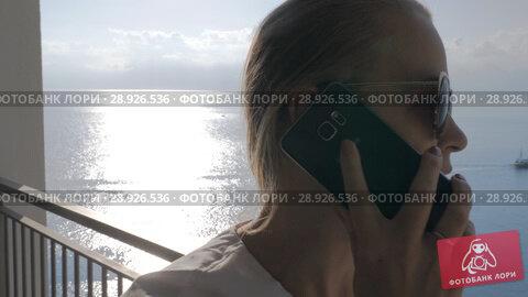 Купить «A woman on a balcony talking to a phone and a sea view behind her», видеоролик № 28926536, снято 2 марта 2018 г. (c) Данил Руденко / Фотобанк Лори