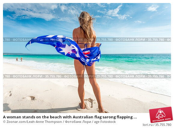 A woman stands on the beach with Australian flag sarong flapping ... Стоковое фото, фотограф Zoonar.com/Leah-Anne Thompson / age Fotostock / Фотобанк Лори